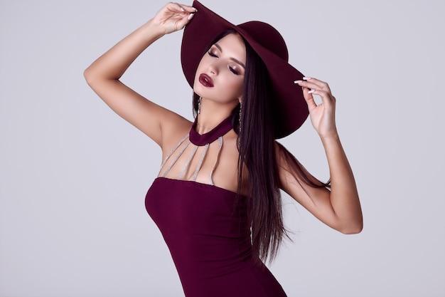 Elegante schöne brunettefrau in einem bunten kleid und in einem breiten hut
