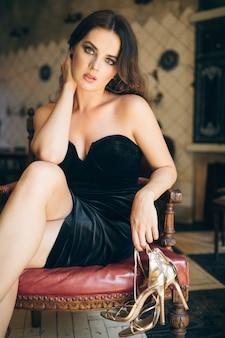 Elegante schöne frau, die barfuß im vintage-café im schwarzen samtkleid sitzt, reiche stilvolle dame, eleganter modetrend, zog ihre schuhe aus, goldene sandalen mit hohen absätzen