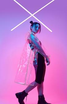 Elegante schöne frau in einem regenmantel um buntes helles neon