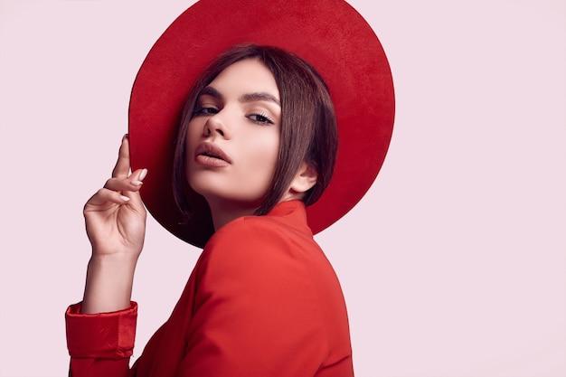Elegante schöne frau in einem roten modernen anzug und in einem breiten hut