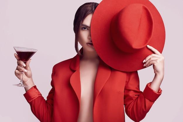 Elegante schöne frau in einem roten modernen anzug und in einem hut mit cocktail