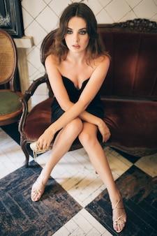 Elegante schöne frau sitzt im vintage-café im schwarzen samtkleid, abendkleid, reiche stilvolle dame, eleganter modetrend, sexy verführerischer blick, attraktive dünne figur