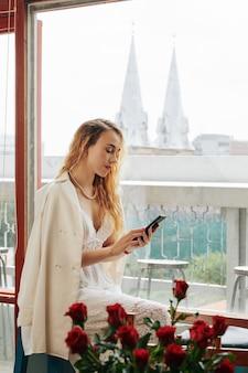 Elegante schöne youg frau, die am fenster steht und nachrichten in ihrem smartphone prüft
