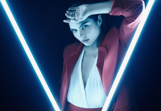 Elegante schönheit in einer roten modernen klage, die mit neonlichtern aufwirft
