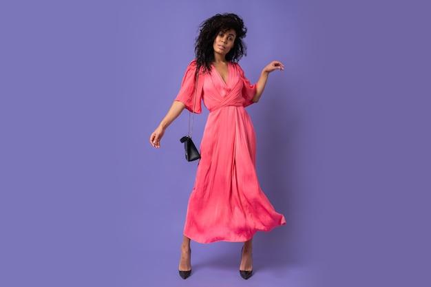 Elegante schwarze frau im rosa partykleid, das spaß über lila wand hat. absätze tragen. volle länge.