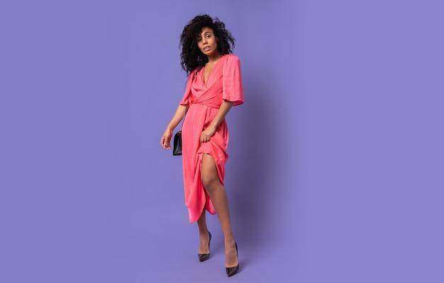 Elegante schwarze frau im rosa partykleid, das über lila wand aufwirft. absätze tragen. volle länge.