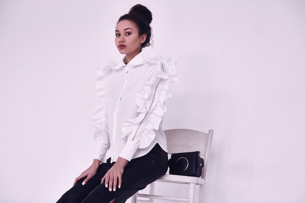 Elegante schwarze frau mit dem gelockten haar im modernen anzug