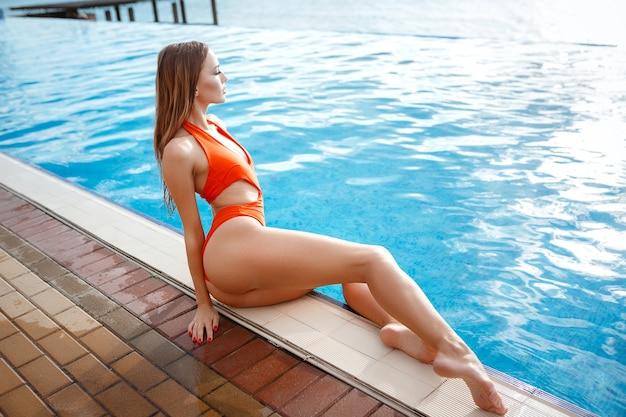 Elegante sexy frau im orangefarbenen bikini auf dem sonnengebräunten schlanken und formschönen körper posiert in der nähe des schwimmbades