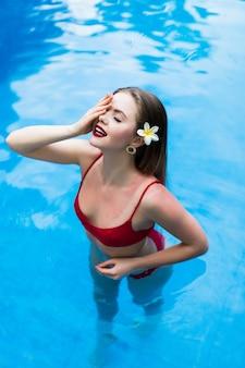 Elegante sexy frau im roten bikini auf dem sonnengebräunten schlanken und formschönen körper schwimmen im schwimmbad