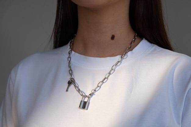 Elegante silberkette der nahaufnahme mit schlüssel- und schlossanhängern auf modell im weißen hemd, metallhalskette