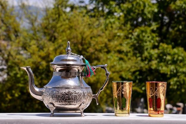 Elegante silberne teekanne mit goldenen gläsern