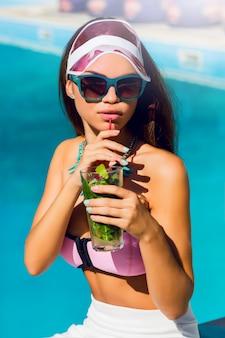 Elegante sinnliche bräunungsfrau in hellen, feuchteren urlaubskleidern, die in der nähe des großen pools sitzen und exotischen cocktail trinken. helle sommerfarben. stilvolle accessoires und sonnenbrillen. strandparty.