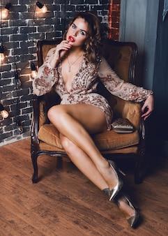 Elegante sinnliche frau, die im luxuriösen sessel sitzt