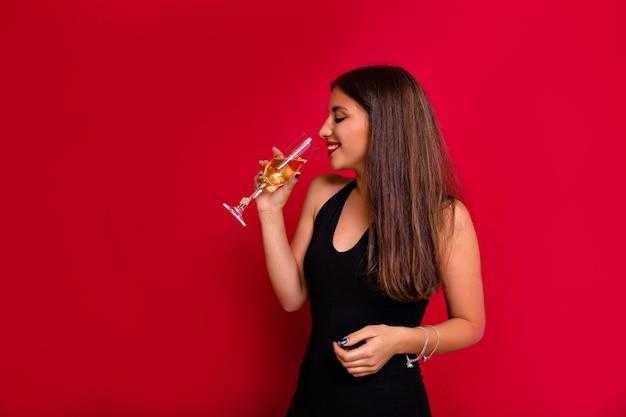 Elegante stilvolle attraktive frau mit dunklem haar, das schwarze kleidung trägt, die champagner trinkt.