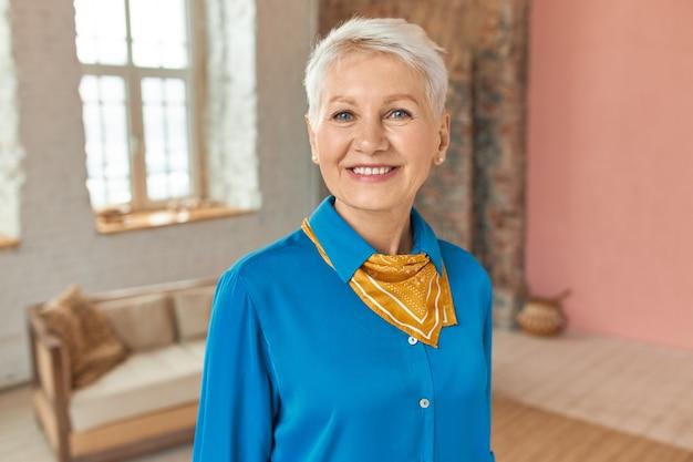 Elegante stilvolle pensionierte frau, die im gemütlichen lebenden roon im blauen hemd aufwirft, um freunde zu treffen, kamera mit freudigem lächeln betrachtend. attraktive reife frau mit kurzen blonden haaren, die drinnen aufwerfen