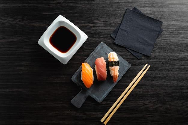 Elegante sushi auf hölzerner tabelle. etwas nigiri mit sojasauce und essstäbchen