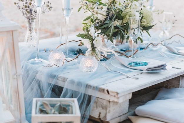 Elegante tabelleneinstellung in den blauen pastellen für eine strandhochzeit
