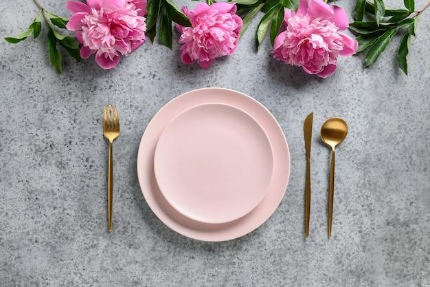 Elegante tabelleneinstellung mit rosa teller verzierten pfingstrosenblumen.