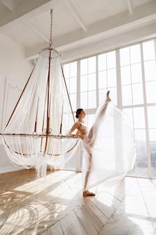 Elegante tänzerin im weißen kleid in der nähe von fenstern