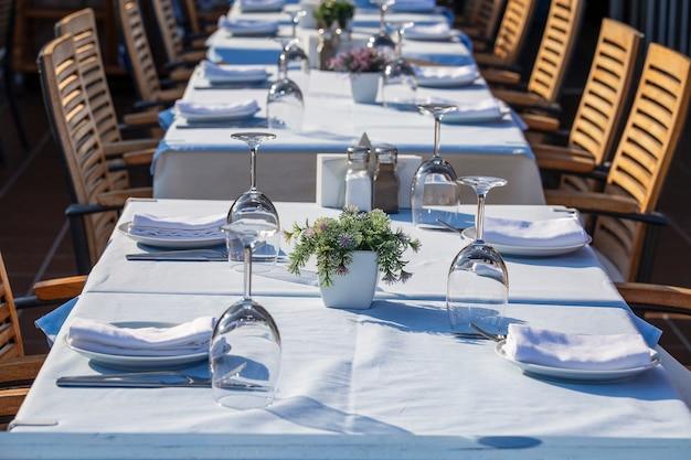 Elegante tischdekoration mit gabel, messer, weinglas und serviette im restaurant