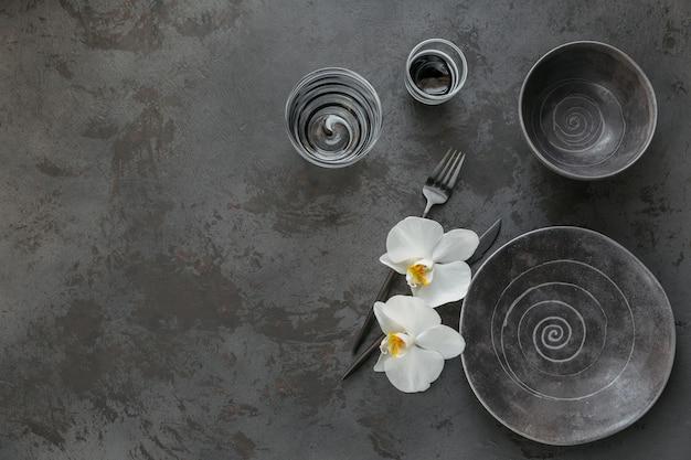 Elegante tischdekoration mit gestrickter grauer serviette, besteck, keramikplatten, gläsern und weißen orchideenblumen auf dunklem tisch. urlaub moderne tischdekoration. romantisches abendessen.