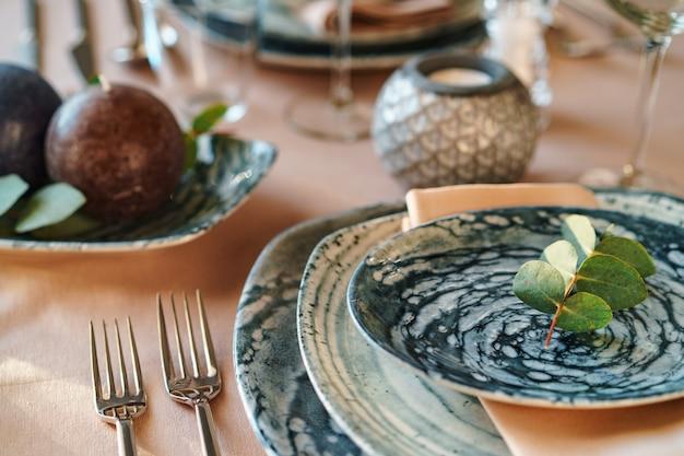 Elegante tischdekoration mit stilvollem grünem geschirr