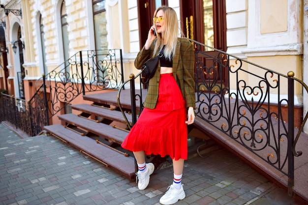 Elegante trendige blonde frau, die auf der straße nahe schönem altem gebäude aufwirft, durch ihr telefon spricht und modisches trendiges hipster-outfit und sonnenbrille trägt, frühlingsherbststil.