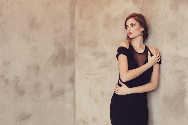 Elegante und glamouröse frau mit schwarzem kleid posiert, modekonzept