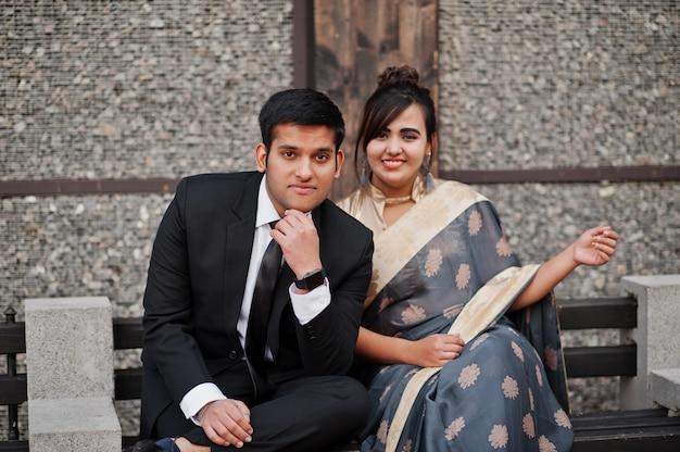 Elegante und moderne indische freundpaare der frau im saree und des mannes in der klage, die auf bank sitzt.