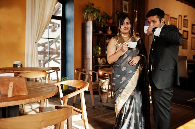 Elegante und moderne indische freundpaare der frau im saree und des mannes in der klage, die auf café sitzt und tee trinkt.