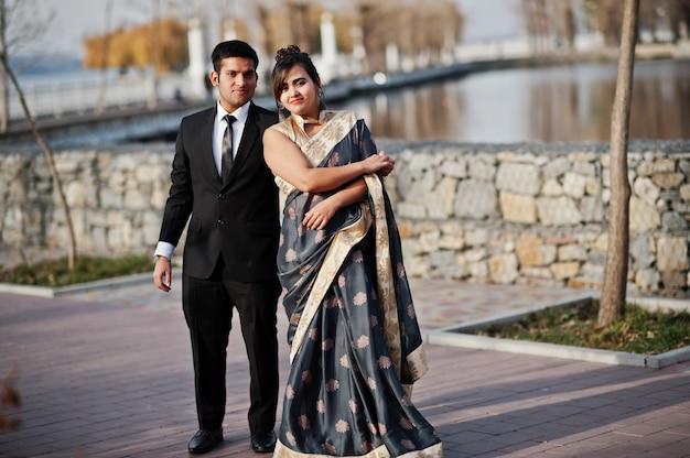 Elegante und moderne indische freundpaare der frau im saree und des mannes in der klage, die zusammen im freien tanzt.