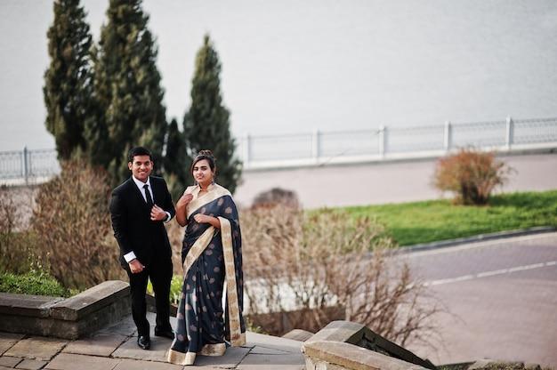 Elegante und moderne indische freundpaare der frau im saree und des mannes in der klage warfen auf treppe gegen see auf.
