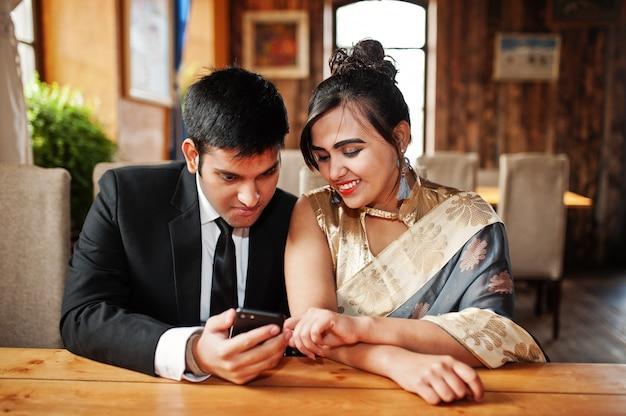 Elegante und moderne indische freundpaare der frau im saree und des mannes in der klage warfen innencafé auf und schauten etwas am handy.
