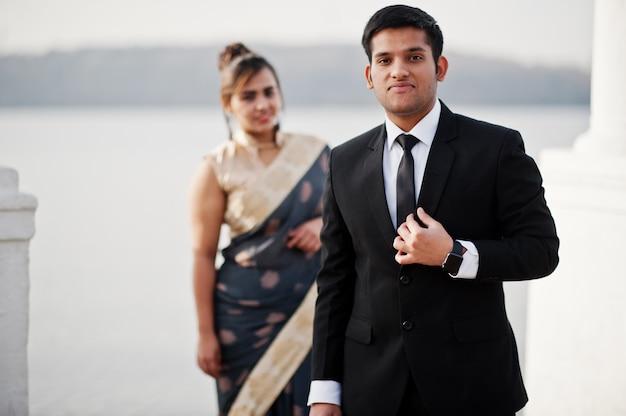 Elegante und modische indische freunde paar frau im saree und mann im anzug posiert am ufer des jachthafens.