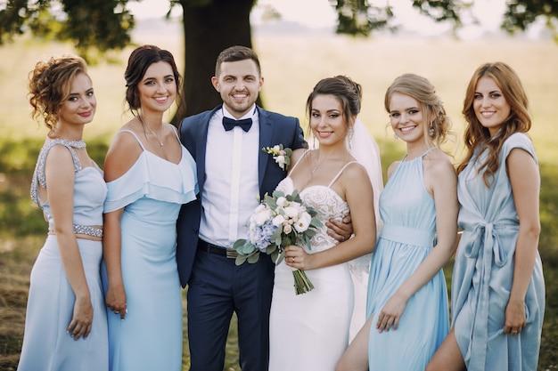Elegante und stilvolle braut zusammen mit ihren vier freunden in blauen kleidern und ihrem ehemann