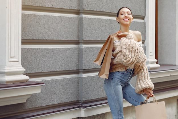 Elegante und stilvolle mädchen auf der straße mit einkaufstüten