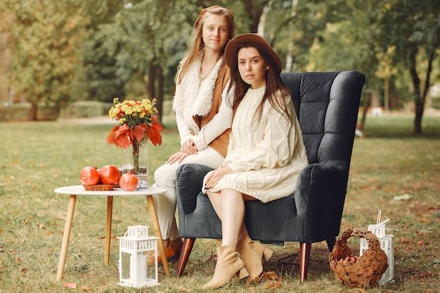 Elegante und stilvolle mädchen, die auf einem stuhl in einem park sitzen