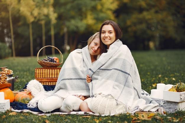 Elegante und stilvolle mädchen, die in einem herbstpark sitzen