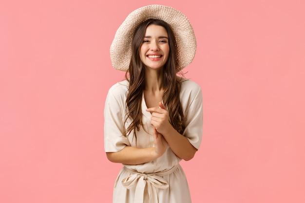 Elegante und weibliche schöne junge frau fasst hände und lächelt, während sie nette ungezwungene unterhaltung mit gruppenfreunden genießt, einkauft, lächelt und begeistert, rosa wand lacht
