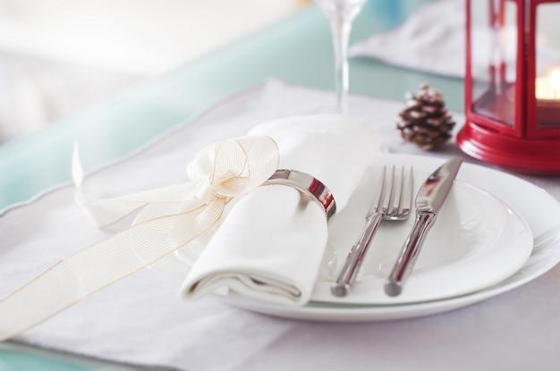 Elegante verzierte weihnachtsgedecke mit modernem tischbesteck, serviette, bogen und weihnachtsdekorationen. weihnachtsmenu-konzept, nahaufnahme, horizontal