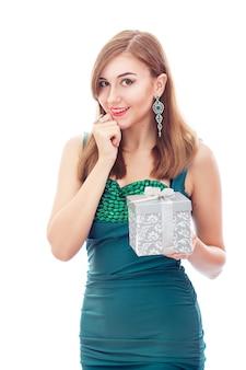 Elegante vornehme frau mit diamantohrringen und -ring. platinschmuck mit grünen und weißen diamanten. geschenk in der silbernen box in ihren händen