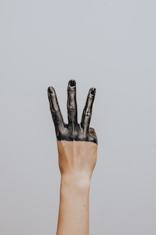 Elegante weibliche hand in schwarze farbe getaucht. isoliert. geste.