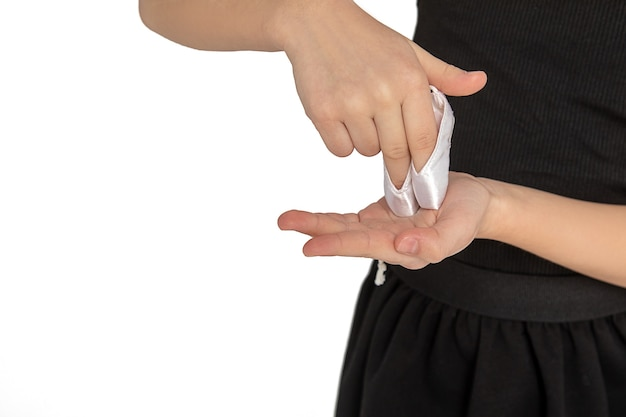Elegante weibliche kinderhände in der ballettspitze lokalisiert auf weißem hintergrund, tanztraumkonzept, studiofoto