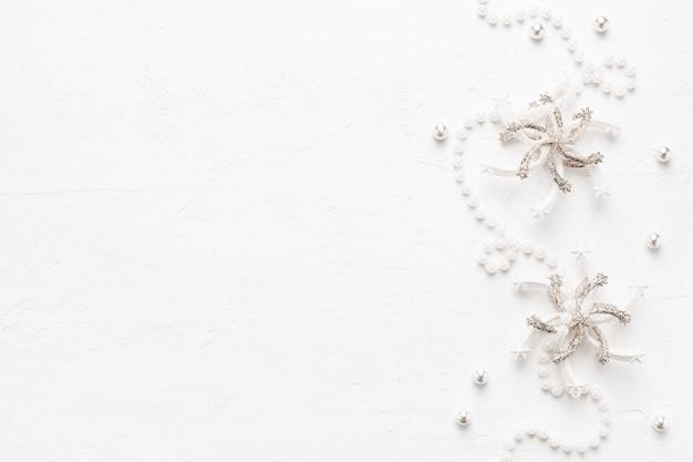 Elegante weihnachtskarte mit perlen und pastelldekorationen auf weiß.