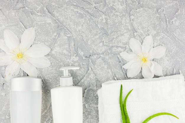 Elegante weiße blumen und flaschen mit aloe