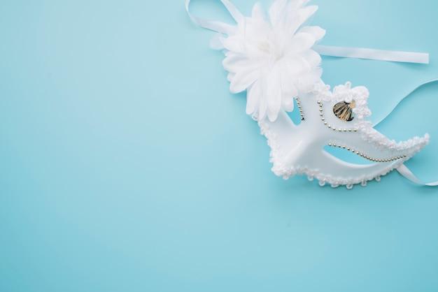 Elegante weiße maske auf blauem hintergrund