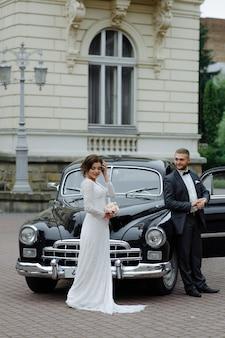 Elegante wunderschöne braut und hübscher bräutigam, die im stilvollen schwarzen auto im licht umarmen.