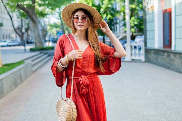 Elegante wunderschöne dame im korallenroten langen kleid, das draußen geht. helle sommerfarben. modischer streetlook.