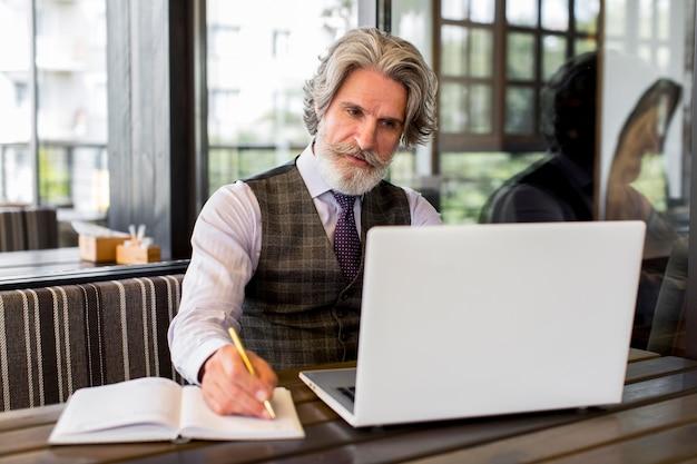 Eleganter älterer mann der vorderansicht, der im büro arbeitet