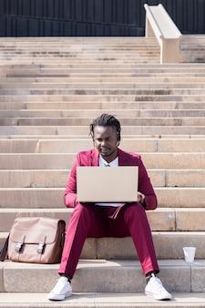 Eleganter afrikanischer geschäftsmann arbeitet mit seinem laptop, der auf einer treppe in der stadt sitzt, technologie- und fernarbeitskonzept, kopienraum für text
